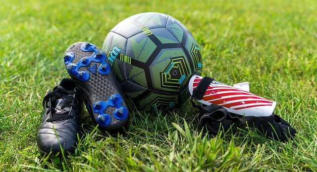 A close up of a toy lying on top of a grass covered field