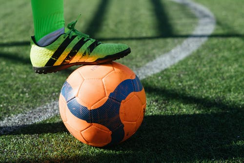 A close up of a football ball on a green field