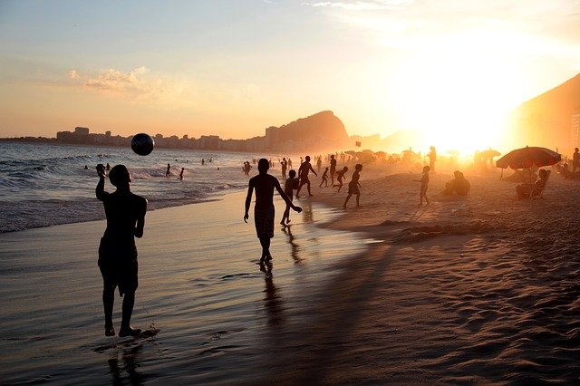 A group of people walking on a beach with a sunset in the background